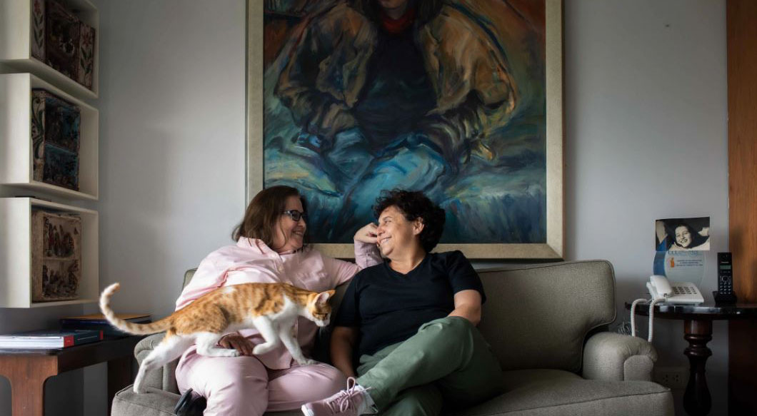Susel and Gracia lovingly look at each other and smile, while sitting on a couch with a cat making its way to their lap.