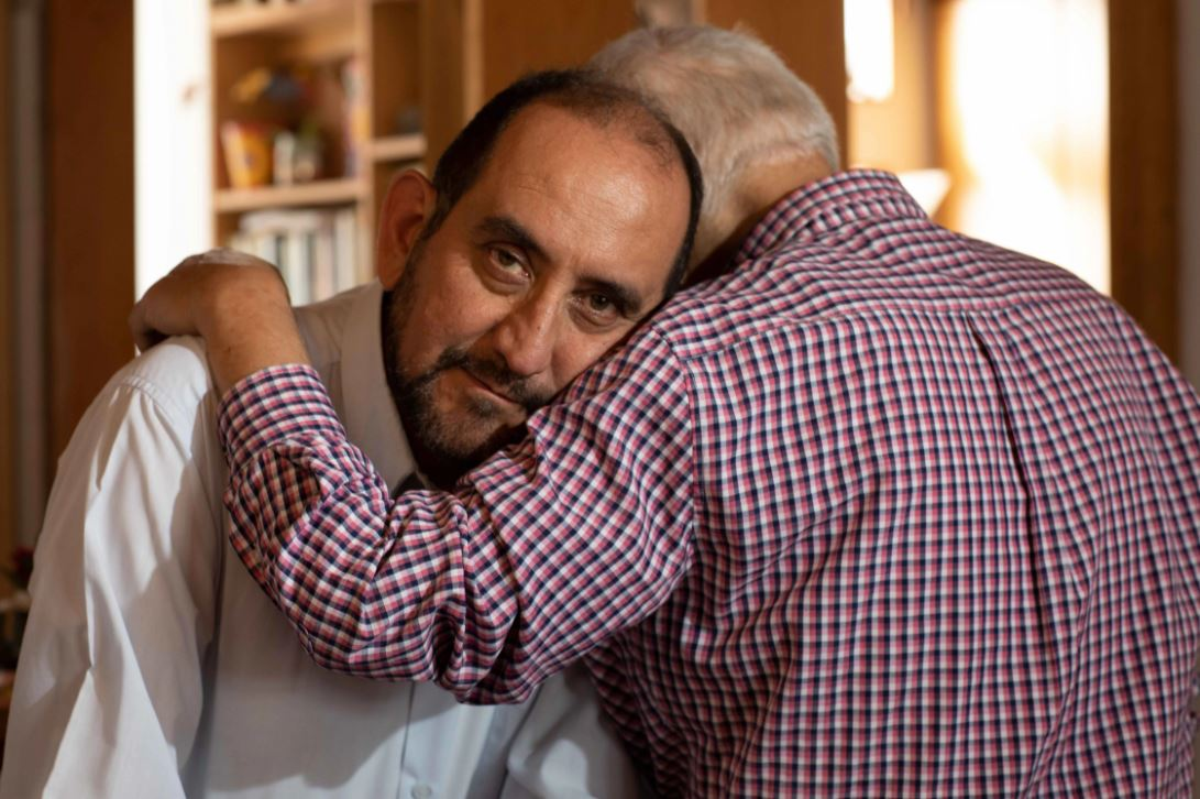 Alejandro faces the camera as Camilo sits opposite him with his back to the camera and his arm lovingly draped around Alejandro.