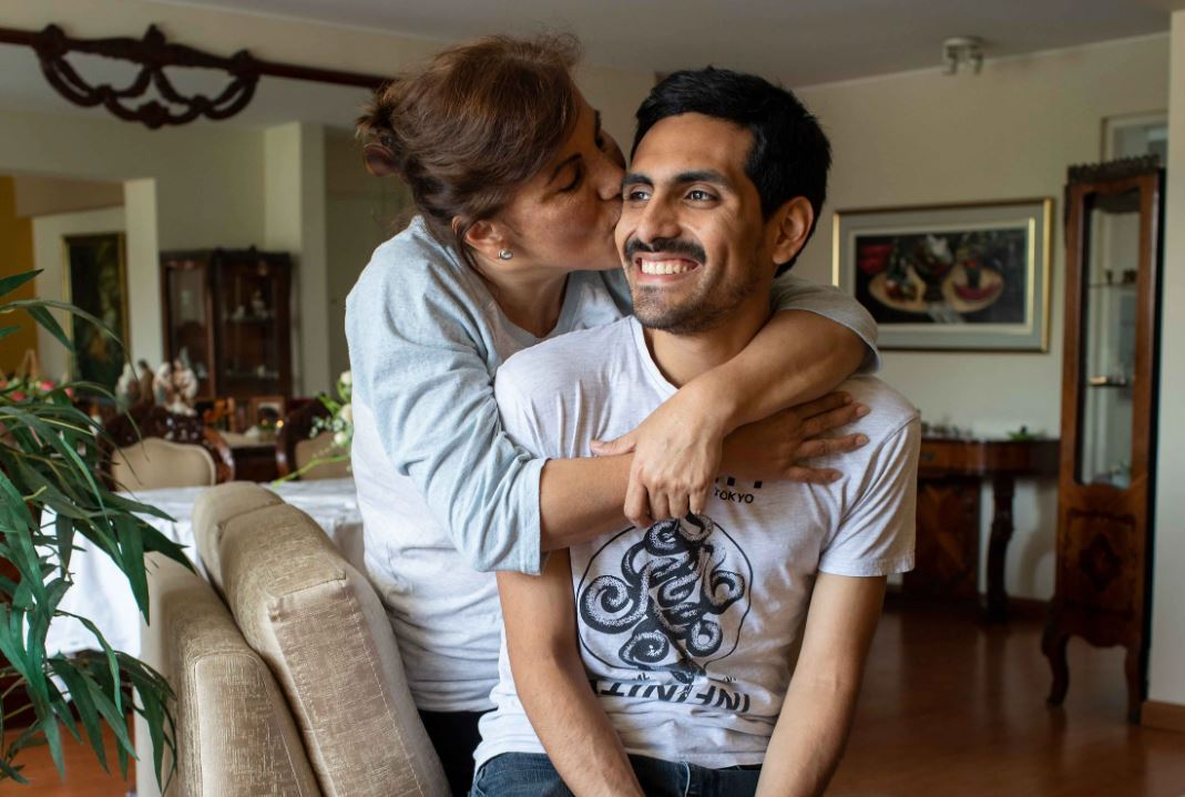 Cecilia, mother, wraps her arms around her son, Carlos, while she kisses his cheek and he smiles.