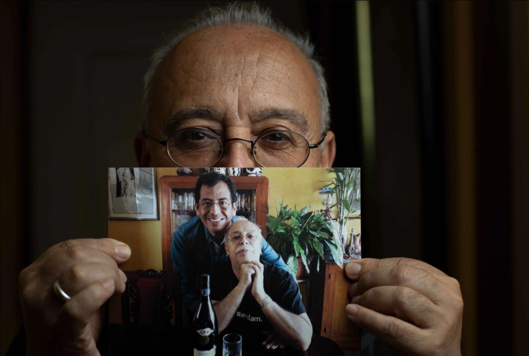 Manolo holds a photograph showing himself and his partner Martín.