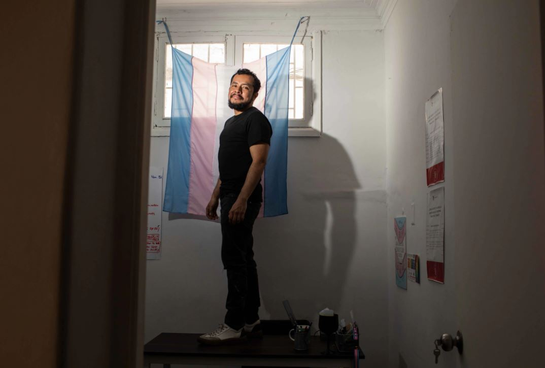 Photo shows Marco standing atop a desk, as he stands in front of a flag draped over a window.