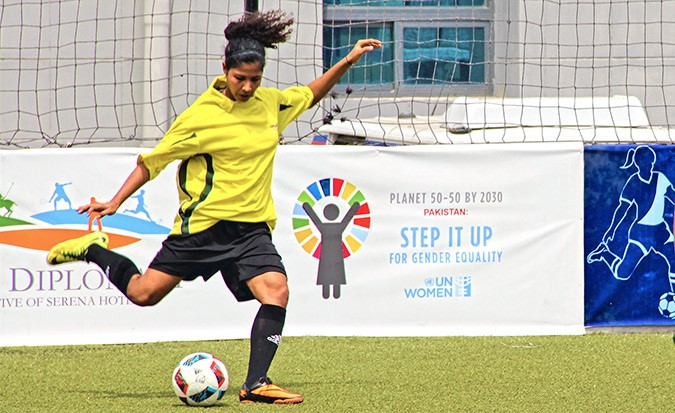Hajra Khan, team captain of the Female National Football Team of Pakistan, is shown kicking a football during a game.