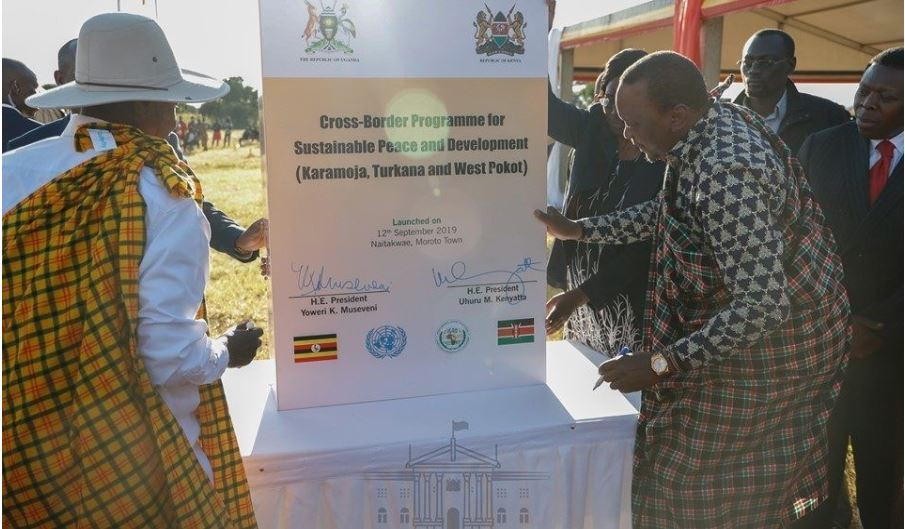 The two country presidents (Kenya and Uganda) are shown signing a signage demonstrating their collaboration.