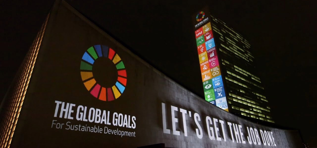 "The UN Building at night showing projected images of the SDGs and text saying ""Let's Get the Job Done""."