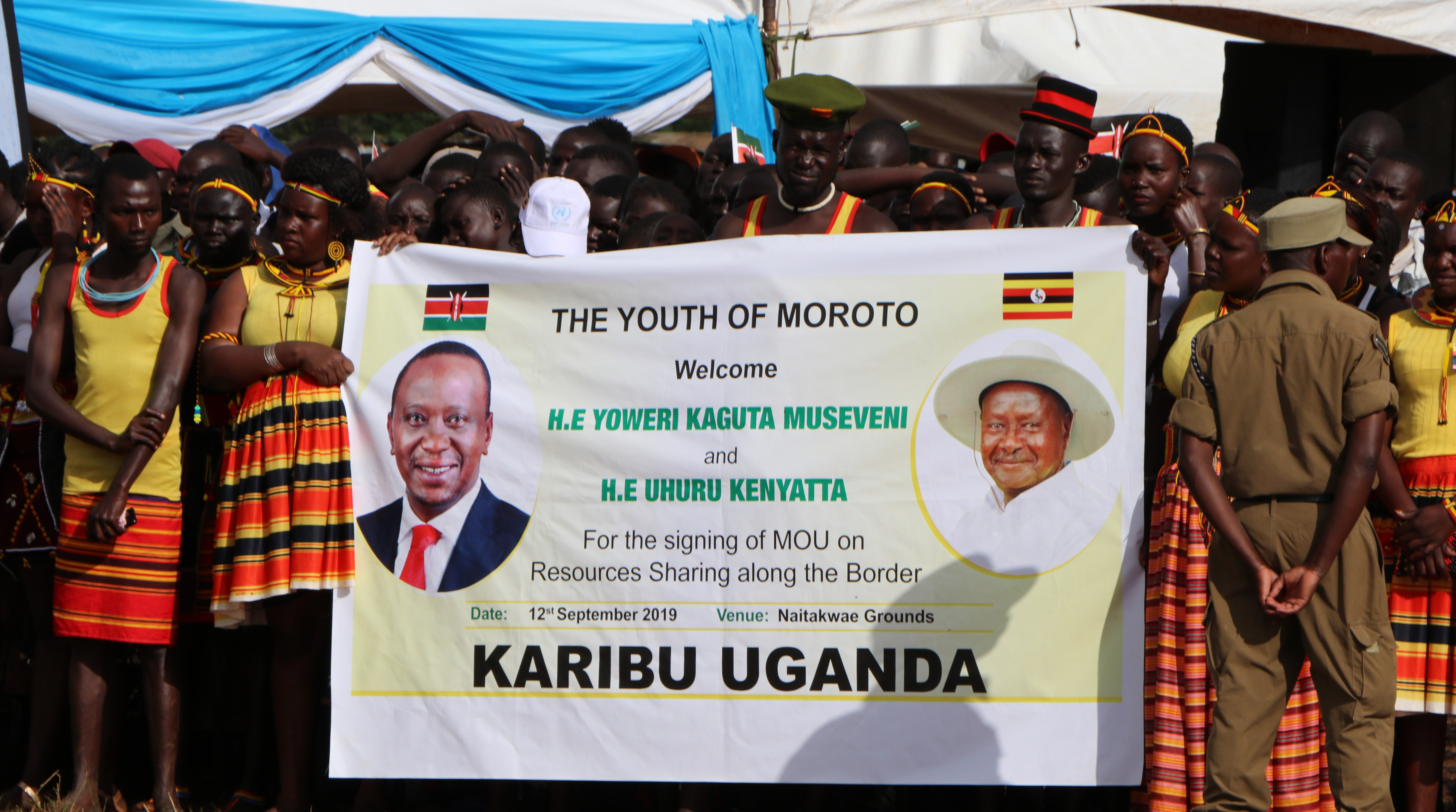 Shows a group of people holding a banner that shows heads of Kenya and Uganda.