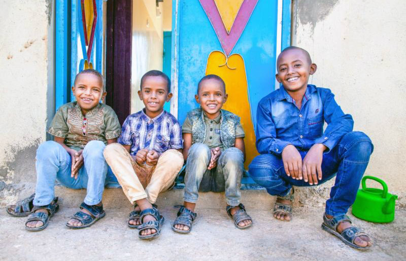 Four young boys sit outside on the step in front of an entrance. They all smile happily at the camera.