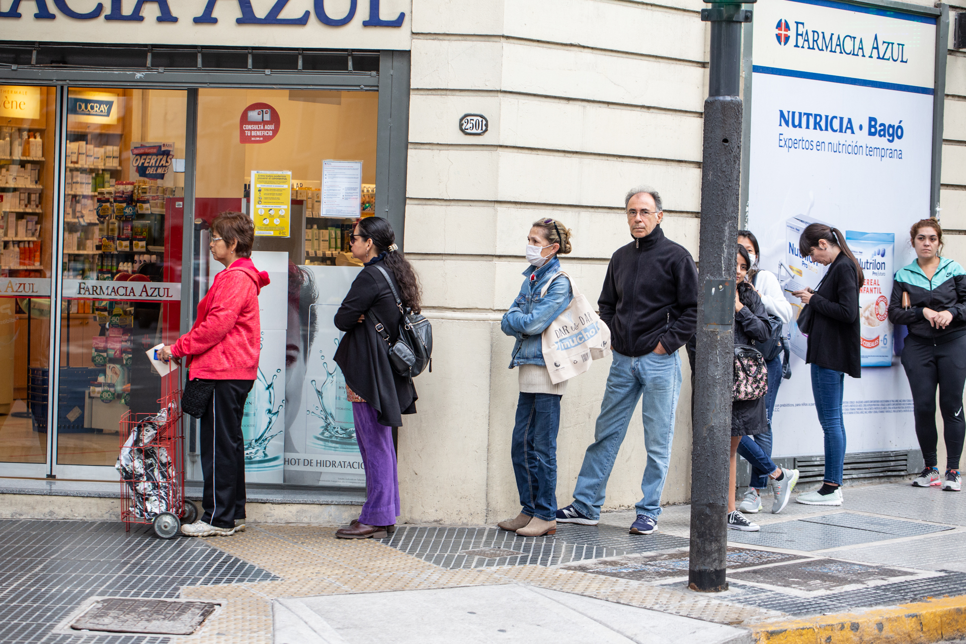 People wait in line outside a pharmacy in Argentina.