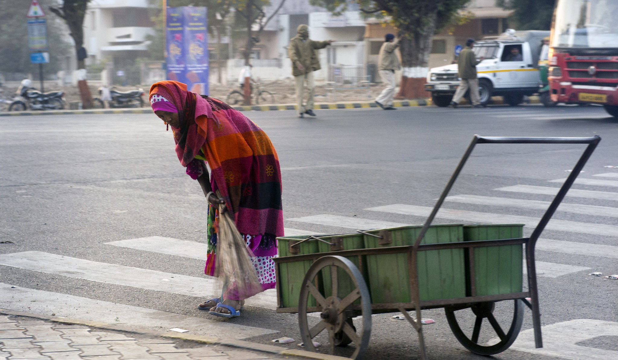 Woman is shown sweeping the street near a cart on the road.