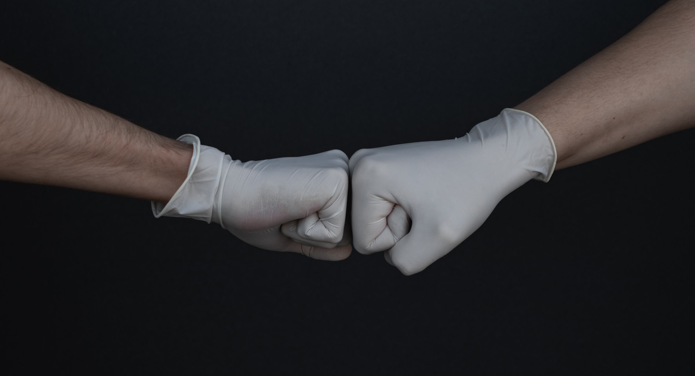Two hands wearing gloves are shown fist bumping against a solid black background.