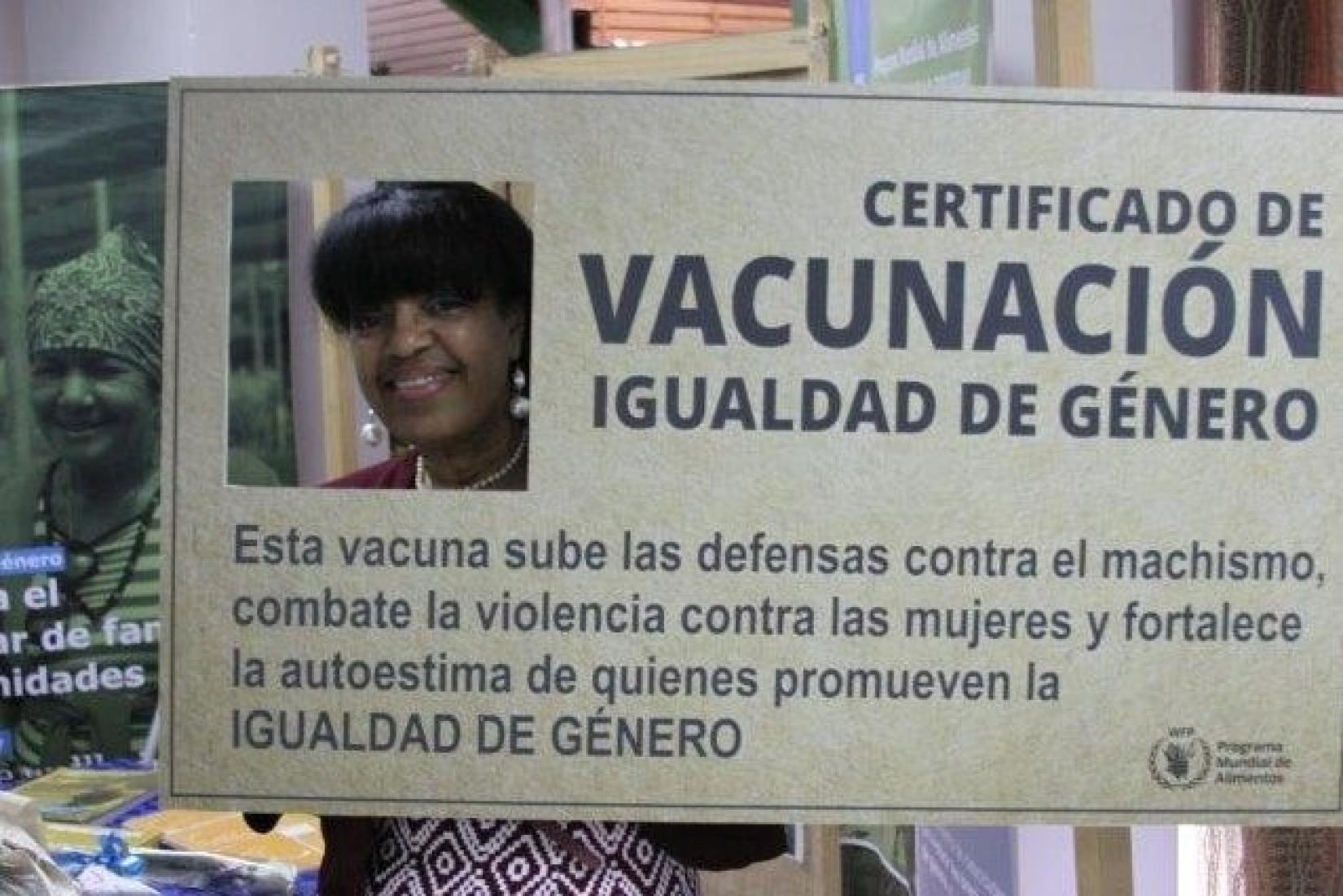 Yudith stands with her head in a cut of a giant-sized gender equality certificate.