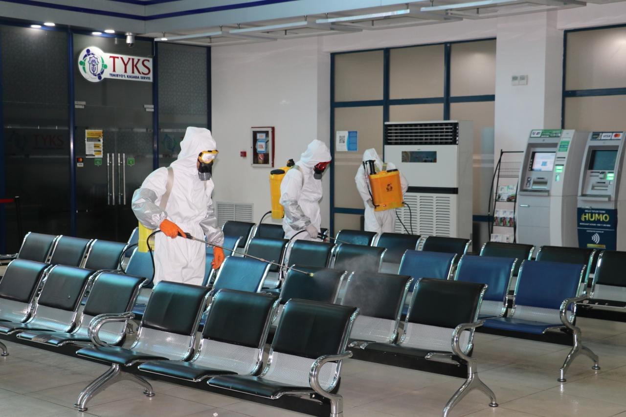 People wearing head-to-toe protective gear are shown cleaning and sanitizing a waiting area.