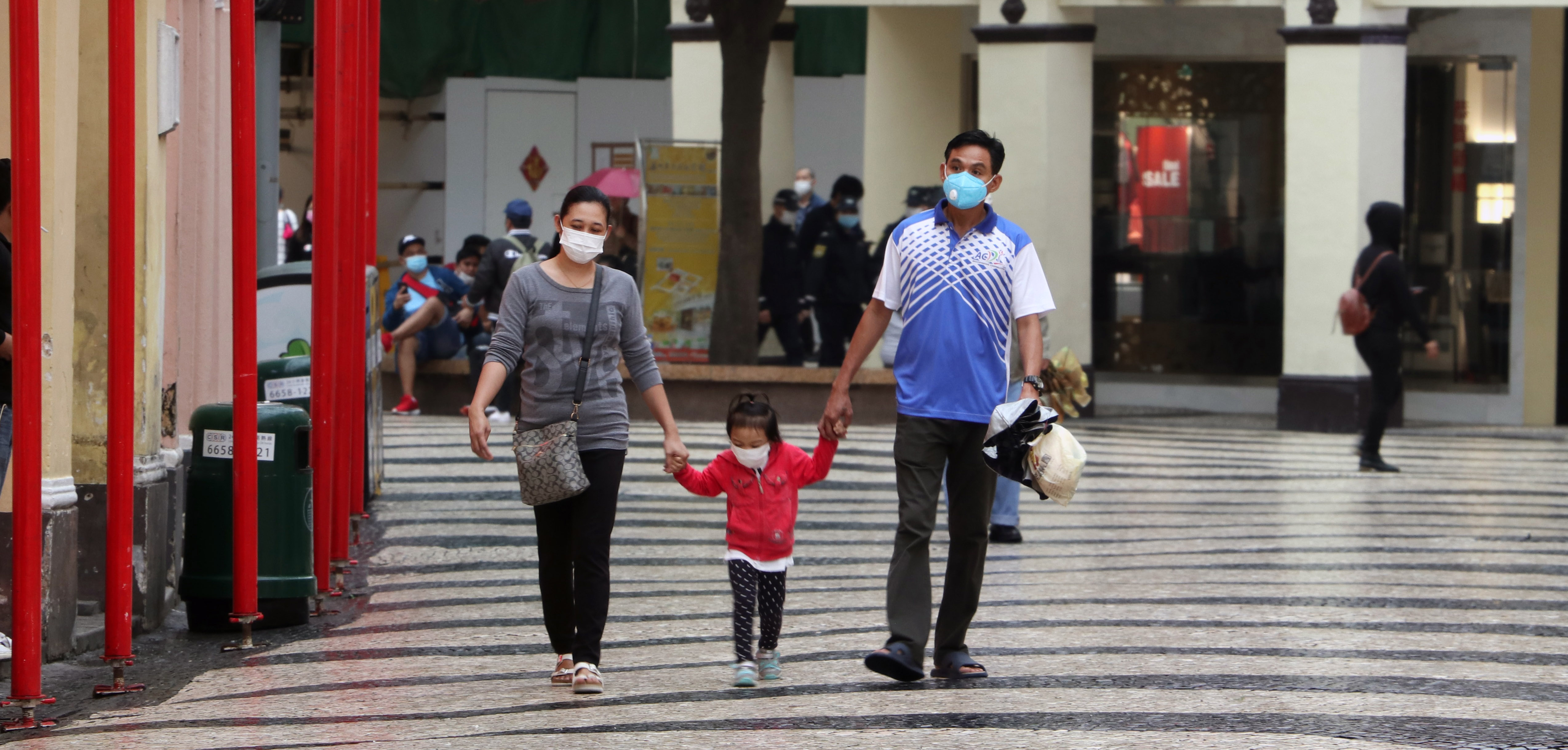 Mother, father and child hold hands as they walk together at a shopping centre, wearing protective face masks.