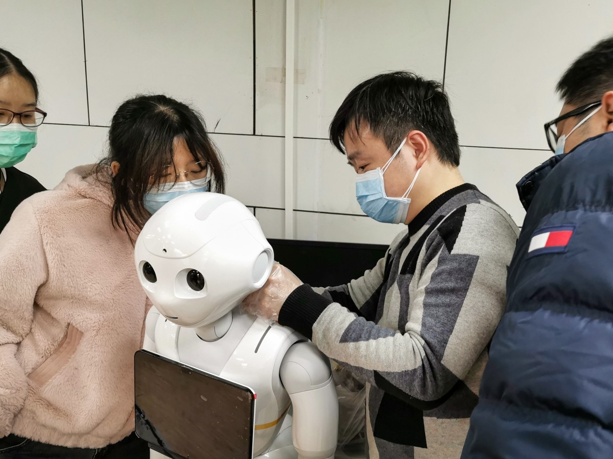 Shows youth handling a robot. Robots are used in many hospitals to deliver food, medicine and other supplies; to disinfect hospitals and other public areas to check patients' temperatures and to answer common questions.