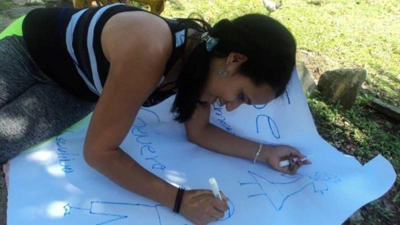 Yudith smiles as she writes on a large sheet of paper, while on sitting on grass.