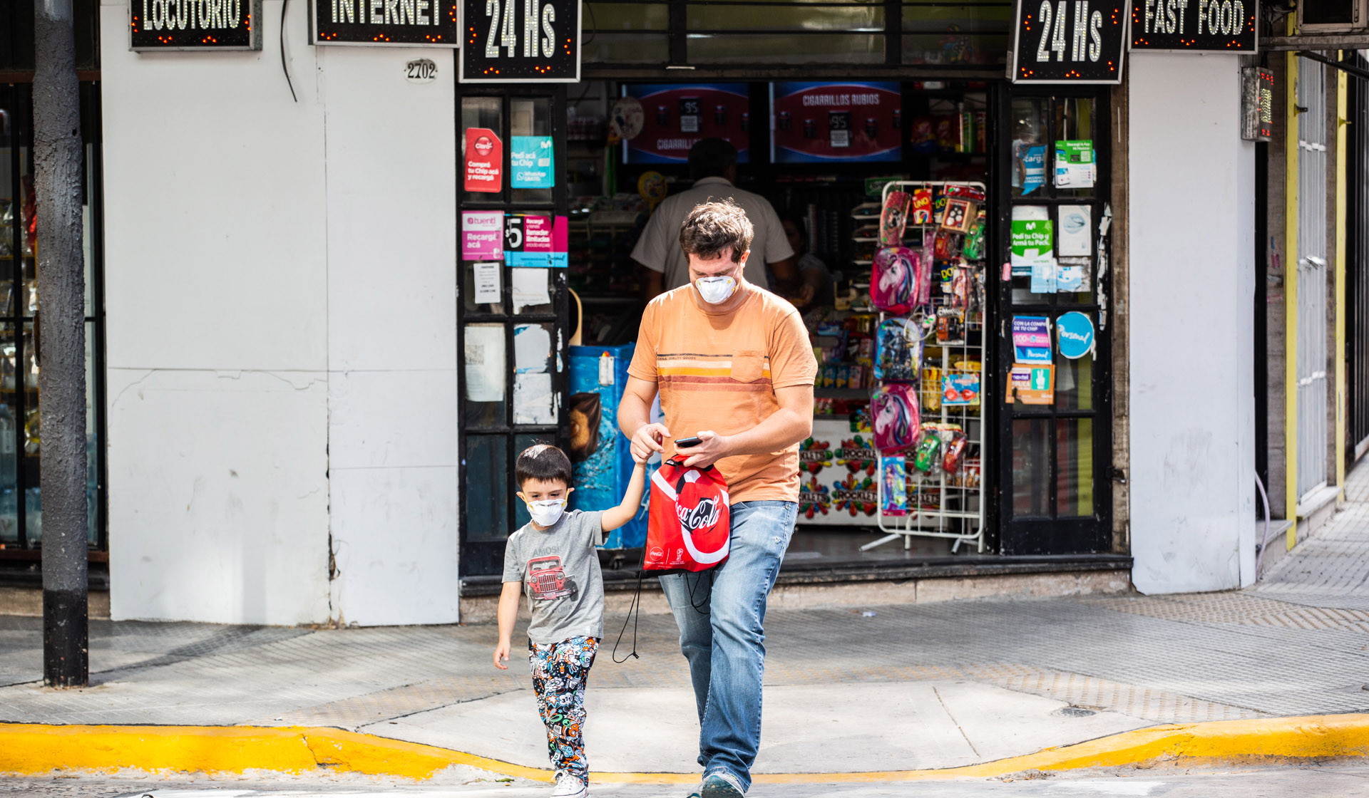 Father and son wearing protective mask leave a store.