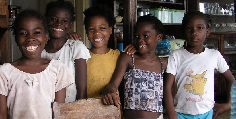Five young girls from São Tomé and Príncipe stand near each other and smile happily at the camera.