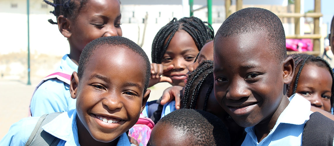 Close up of children from Beira, one of Mozambique's largest cities, happily smile at the camera in front of a playground.