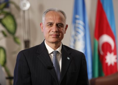 Official photo of the Resident Coordinator, Ghulam M, Isaczai, in front of the UN and Azerbaijan flag.