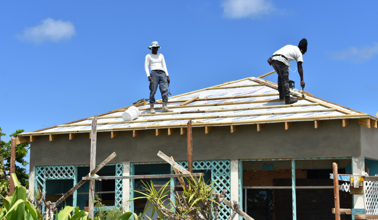 Two men work on rebuilding and preparing a home for future natural disasters.
