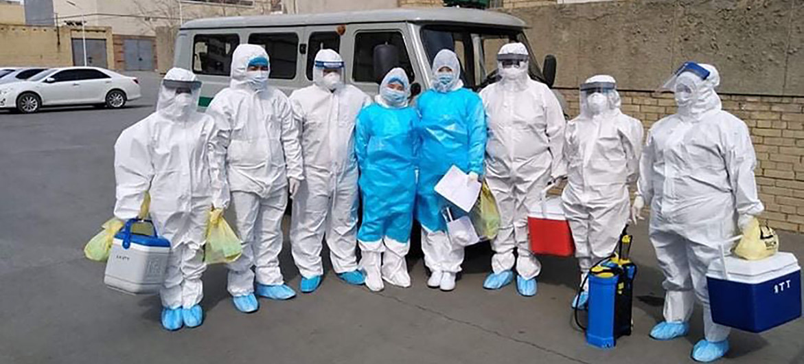 National Centre for Communicable Diseases team stands side-by-side in front of a van wearing full head-to-toe protective gear.