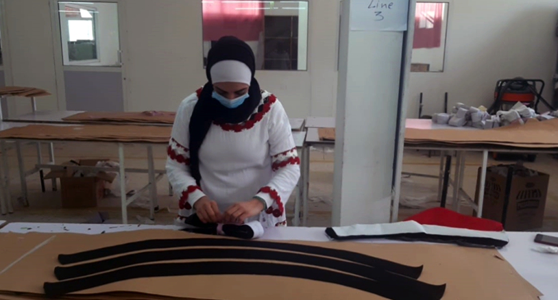 A woman wearing a protective face mask concentrates on a garment in a manufacturing space.