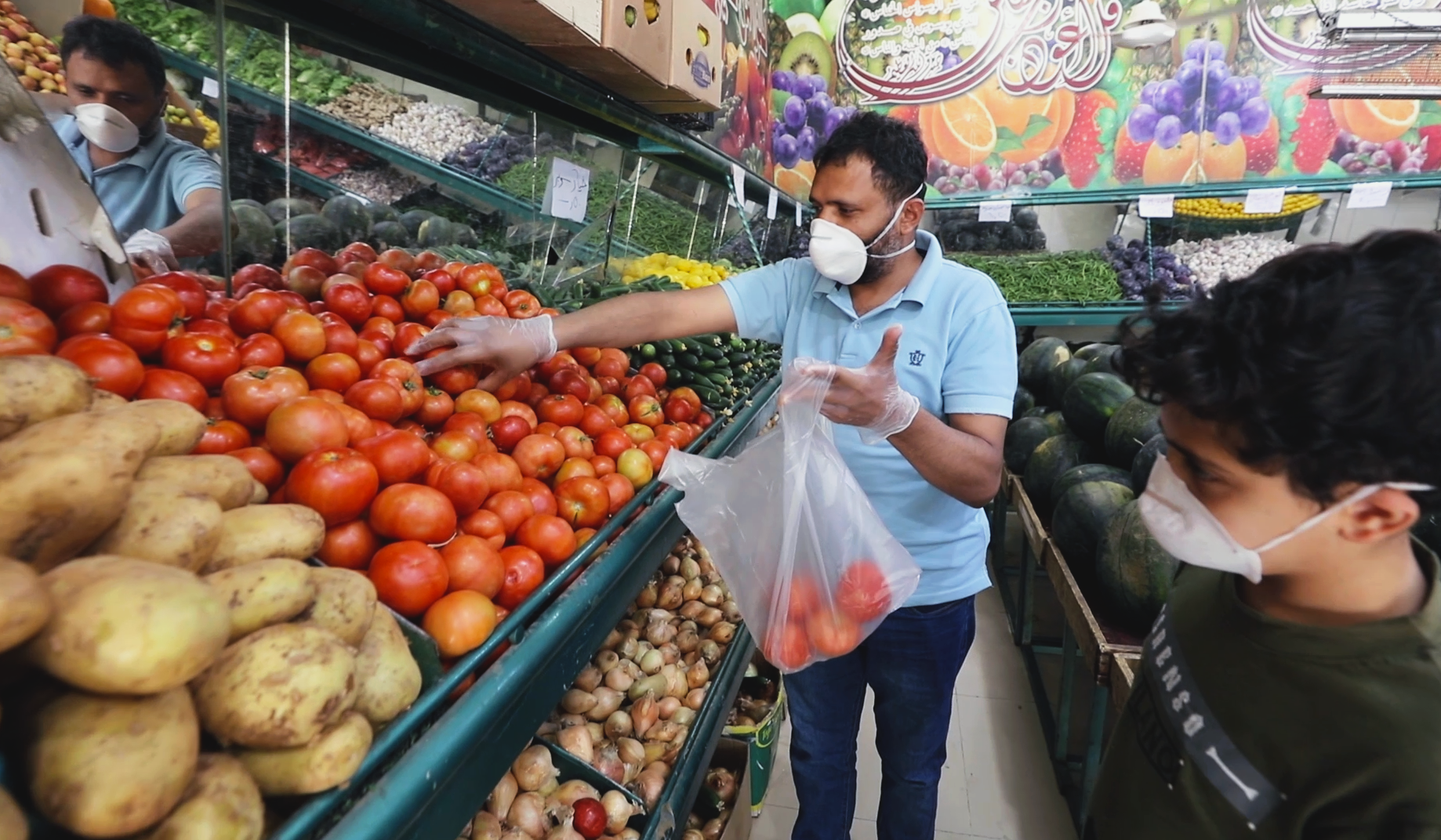 Abdou, a Yemeni refugee in Amman, shops in one of the grocery after the reopening of small shops.