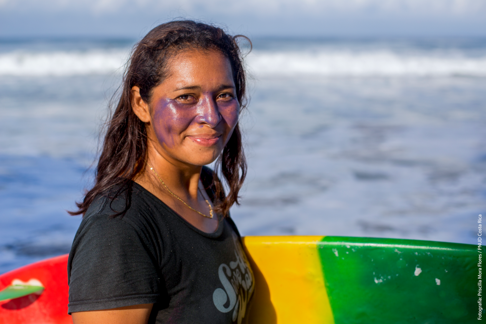 A female surfer smiles as she holds her surfboard by the shore of a beach.
