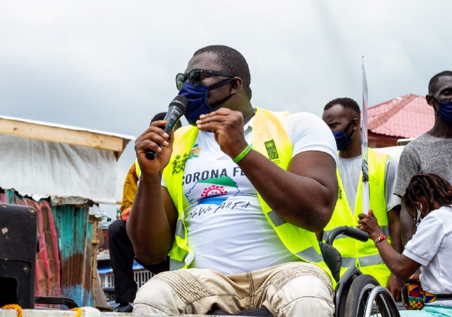 A photo of George Wyndham, a Paralympic medalist from Sierra Leone, in his wheelchair and speaking into a microphone to address a crowd