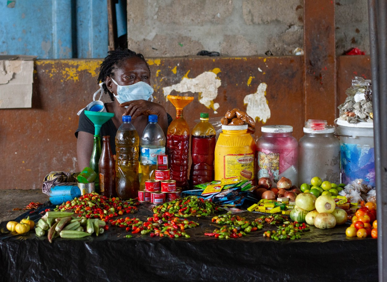 Photo of a woman wearing a face mask while sitting behind her stall selling various goods at the Freetown market