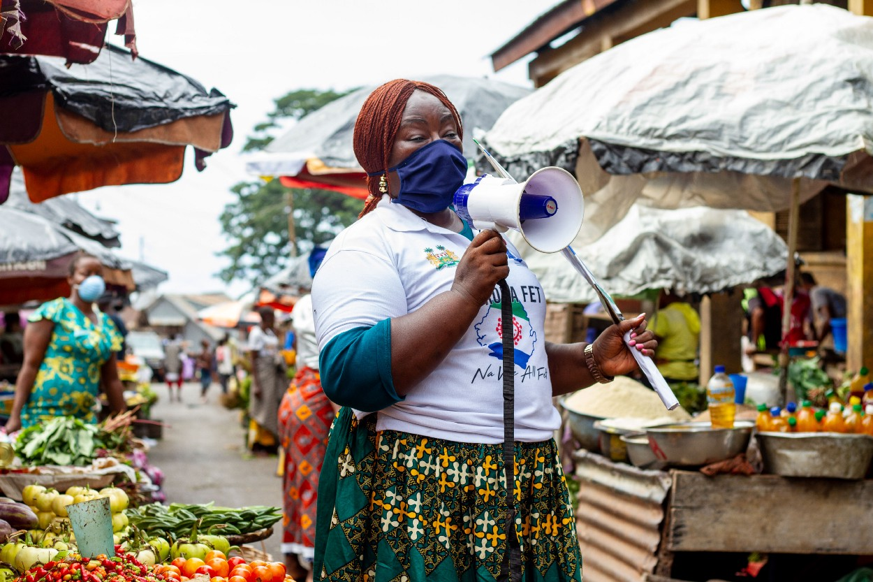 A community mobilizer speaks into a megaphone while standing in the middle of a market in Sierra Leone