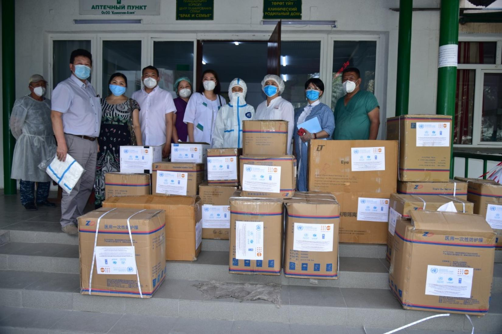 UN personnel and healthcare workers stand behind donation boxes wearing protective gear.