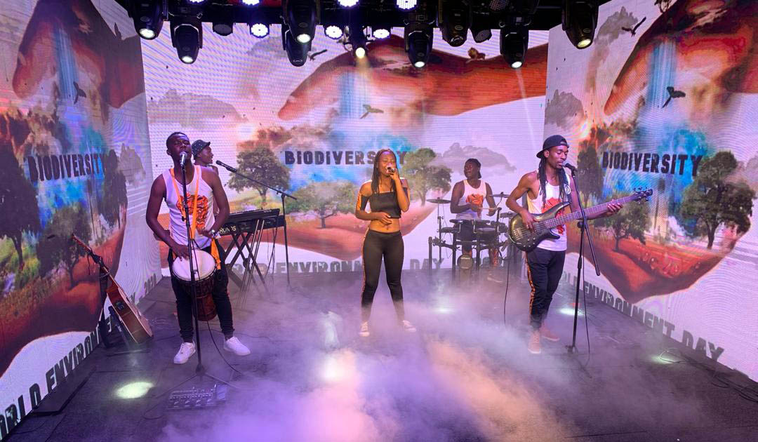 "Caroleen Masawi and her band perform surrounded by green screens featuring images of the globe and the term ""Biodiversity"" featured on them."