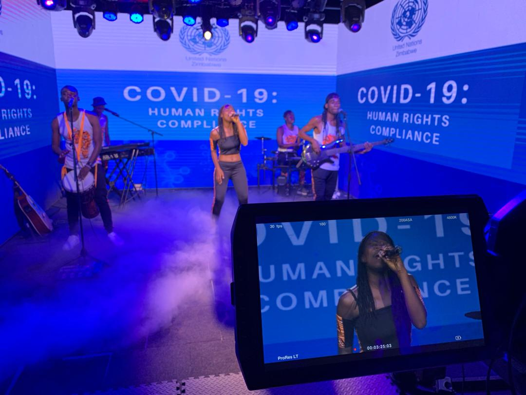 Caroleen Masawi and her band perform surrounded by green screens featuring a COVID-19 message.