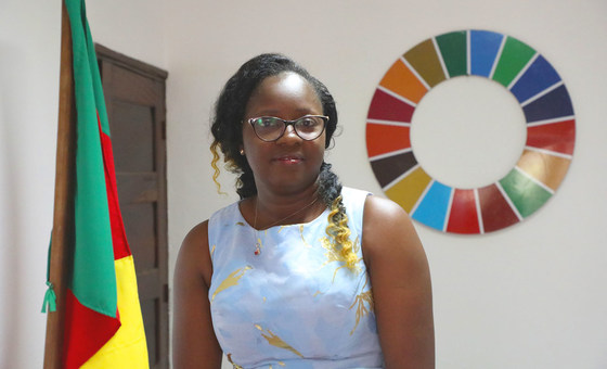 Photo showsCecile Mawe, founder and President of Jeunes en Action pour le Développement Durable (JADD), Cameroon., besides the Cameroon flag and the SDG wheel.