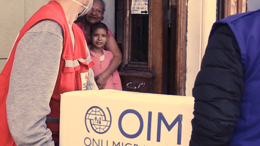 IOM staff carry a box of donations into a family's home.