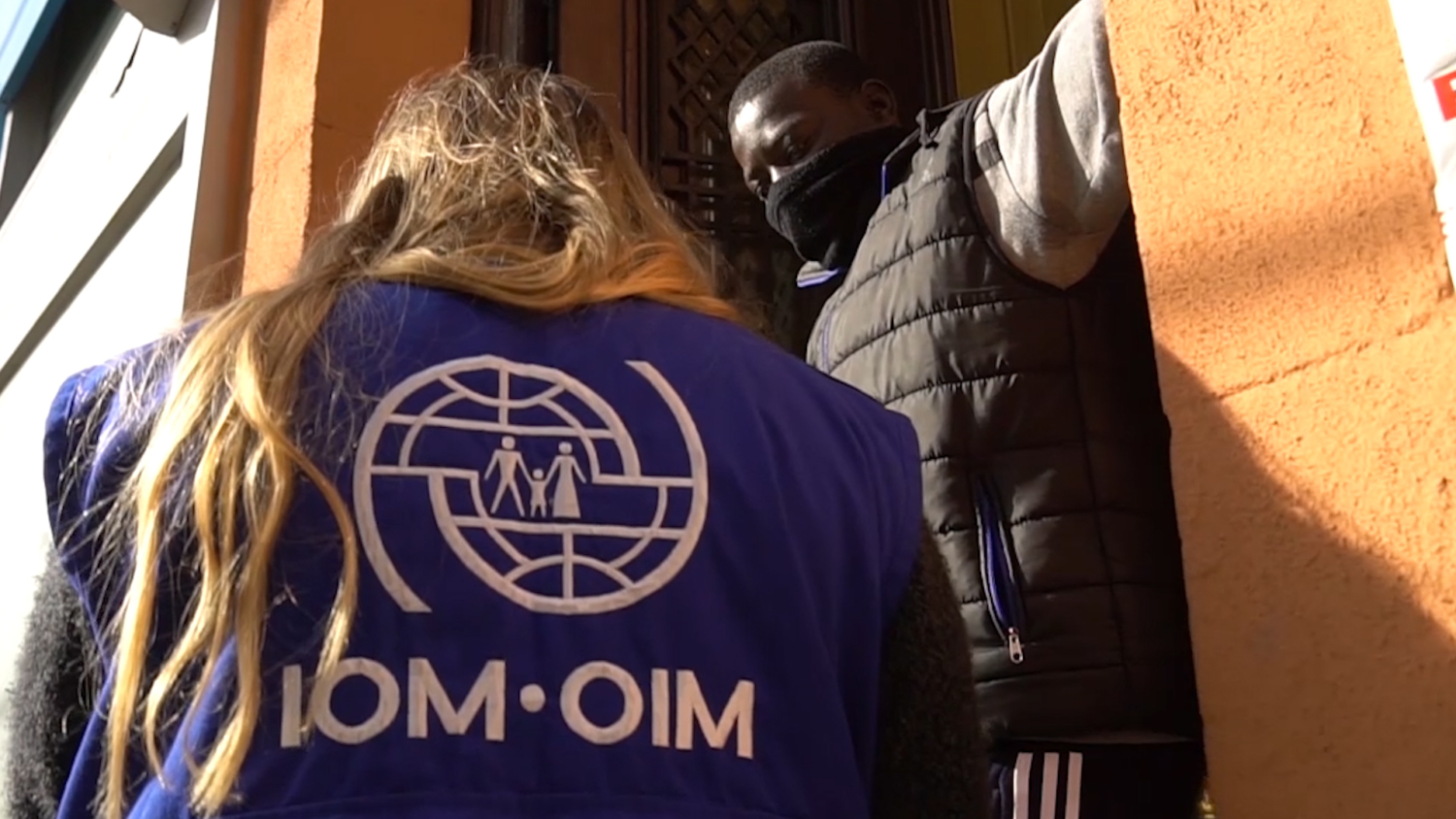 An IOM Staff speaks to a man at the entry to his home.