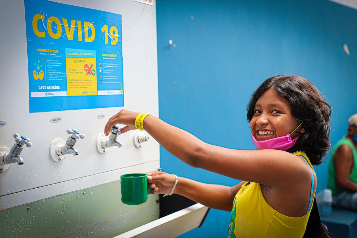 A young Venezuelan girl wearing a mask under her mouth happily smiles as she prepares to fill her mug at a drinking water station at a shelter.