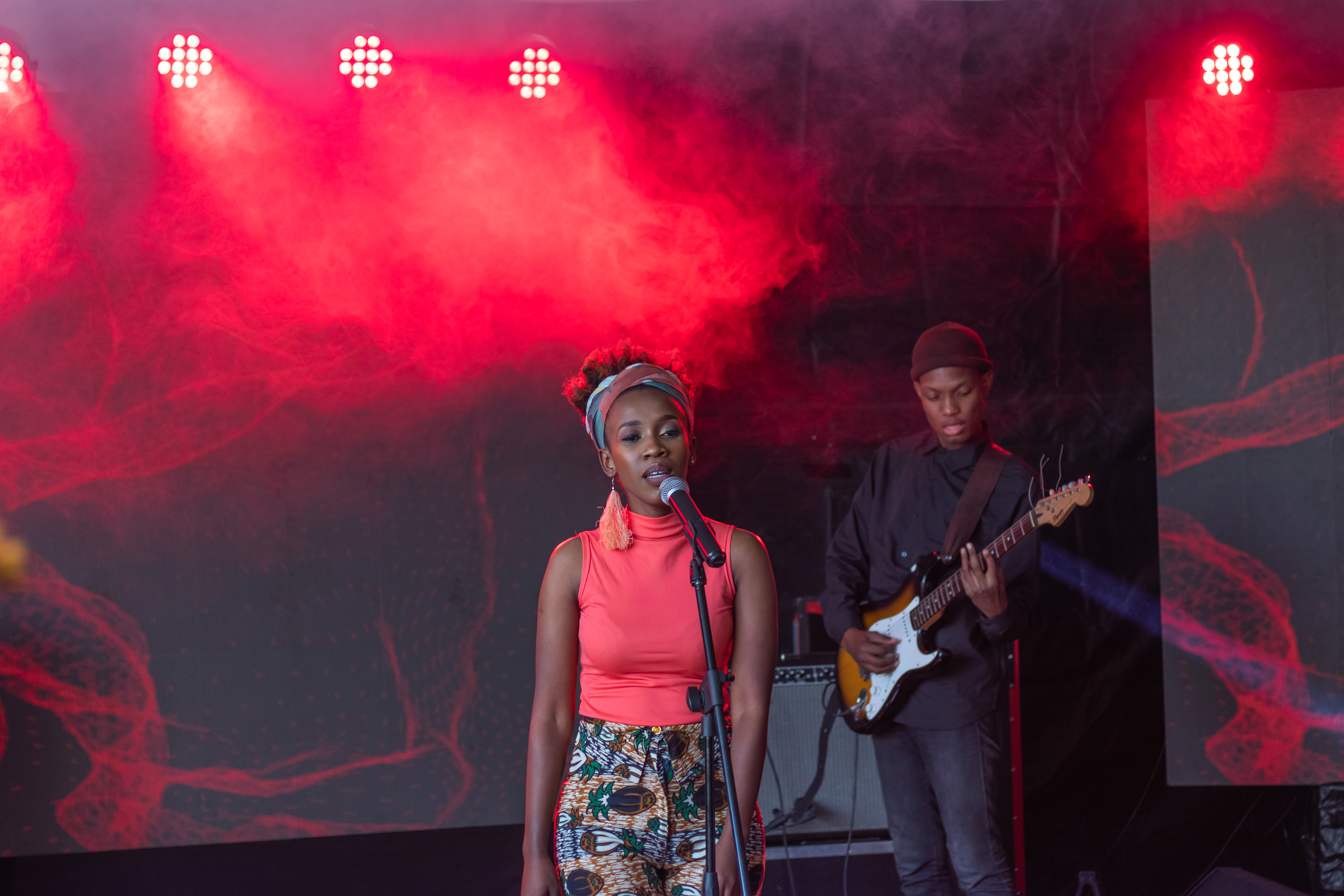 Musician Vuyo Brown sings at a microphone, while her bassist plays in the background.