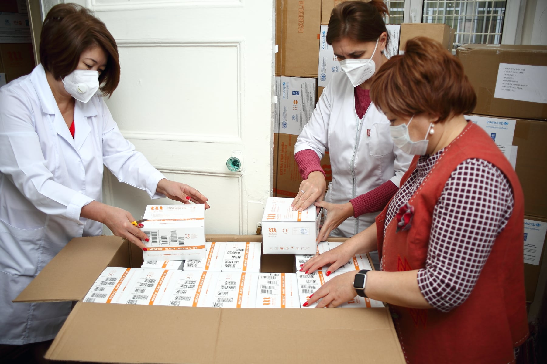 Healthcare workers open boxes of donated syringes and essential supplies to support those of higher risk, including those with diabetes.