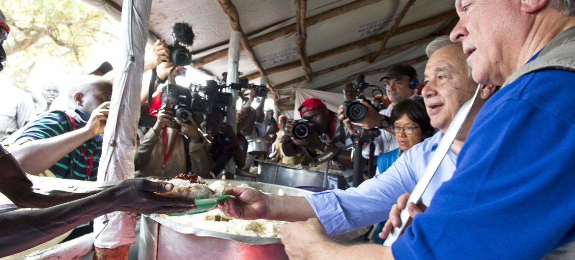 Secretary-General António Guterres (second from right) with David Beasley (right), WFP Executive Director, serving meals at the reception area for newly arrived refugees at the Imvepi settlement in Uganda.