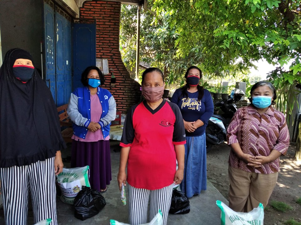 Women standing proud with their protective masks at Peace Village in Jetis, Central Java.