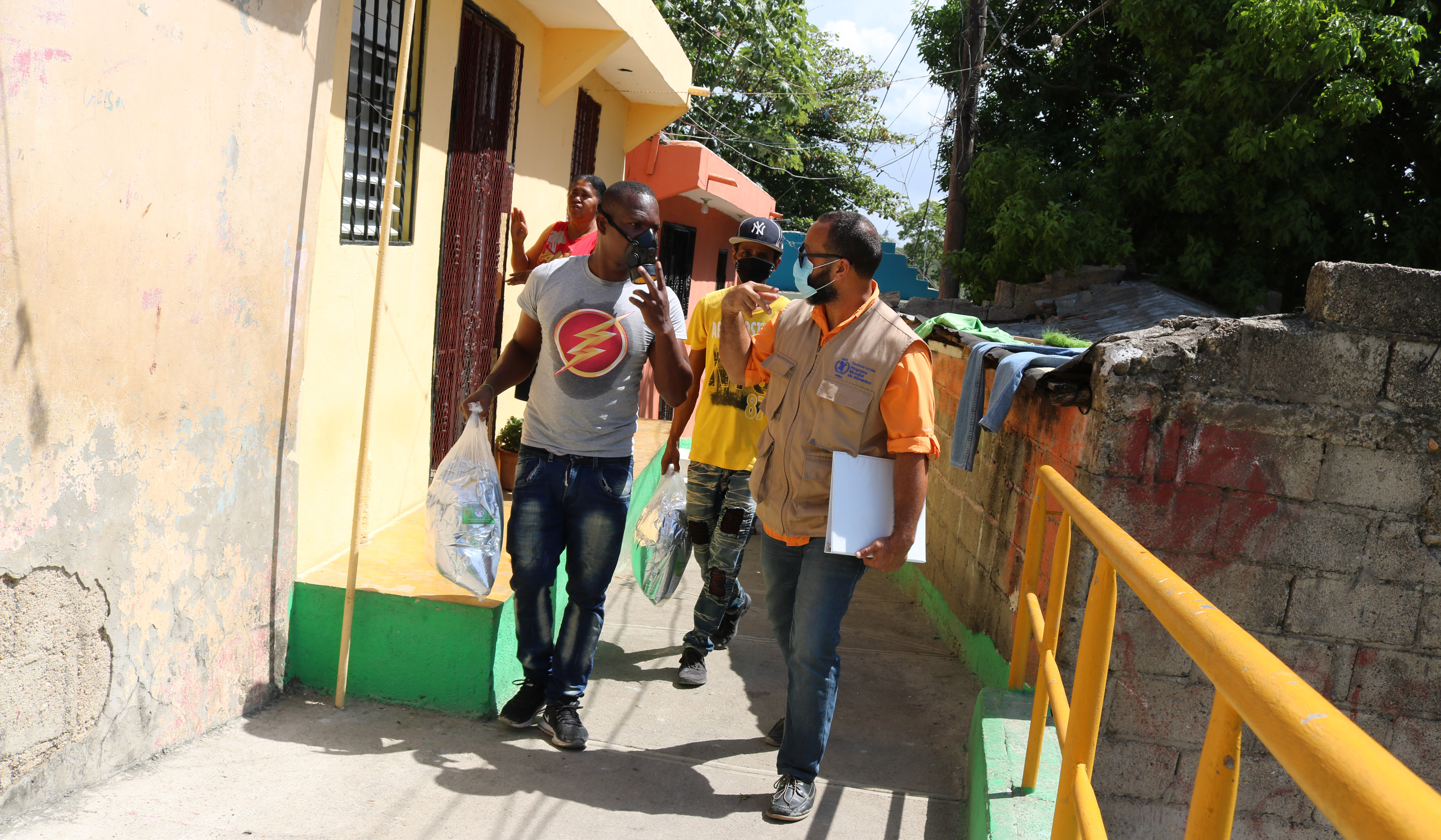 UN staff with local residents walk along homes in a neighbourhood in the Dominican Republic.