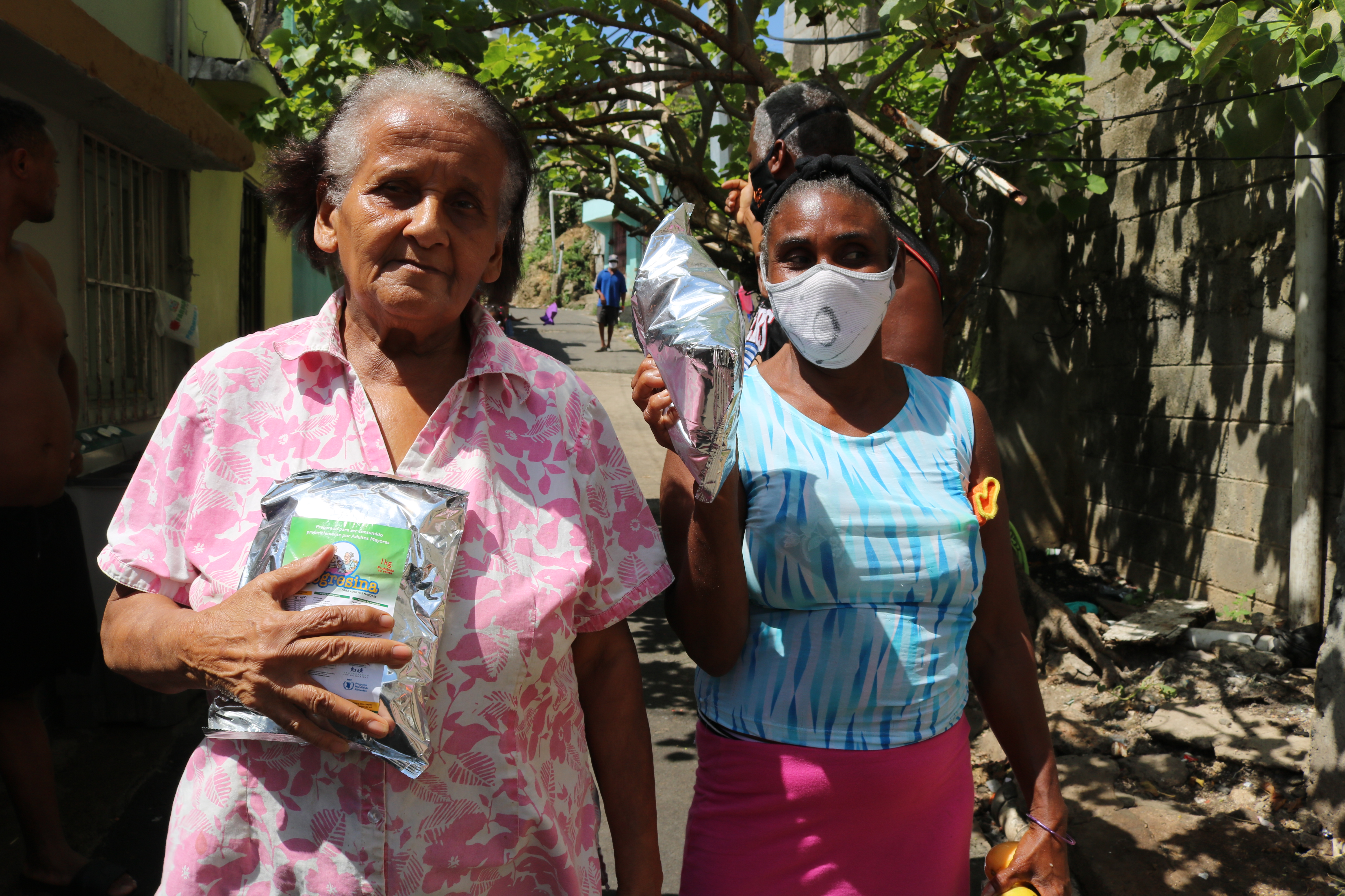 Two women prominently hold the food supplies received from the World Food Programme.