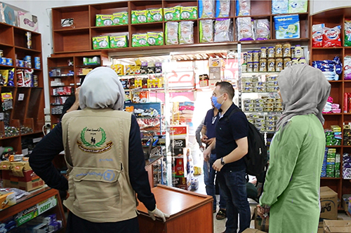 People are shown at a local store using, where the e-vouchers are accepted.