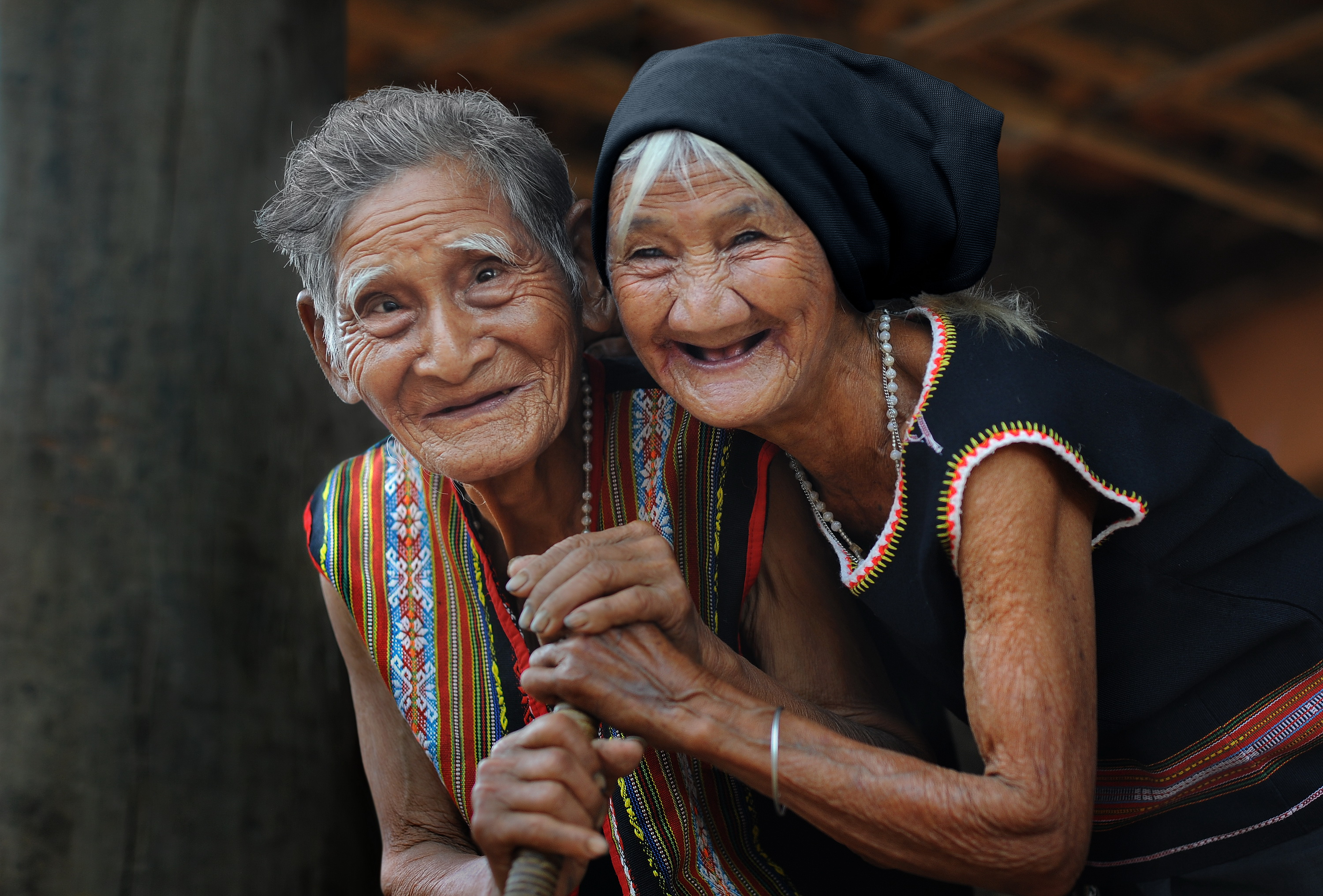 Two cheerful older women look happily at the camera.