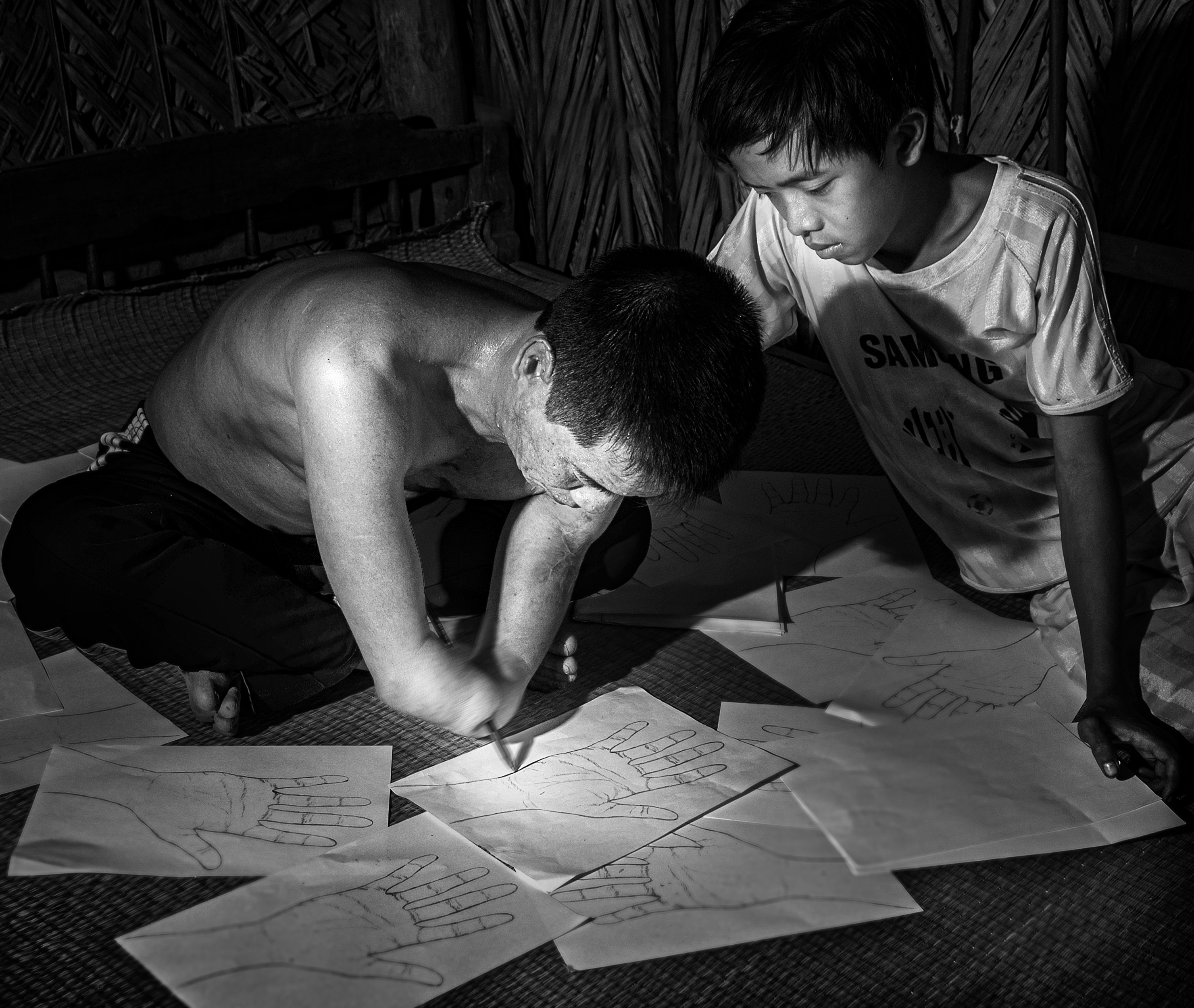 Black and white photo of a man and boy. The man has an amputated hand, sit together on the ground drawing and writing on sheets of paper.
