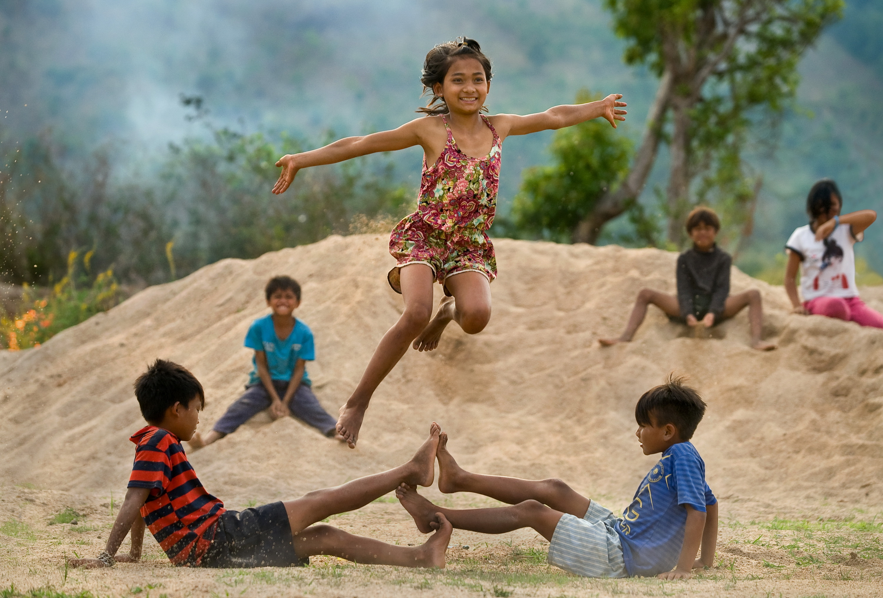 Children play outside. Two boys are on the ground touching their feet, while one girl is frozen in the air happily jumping above them.