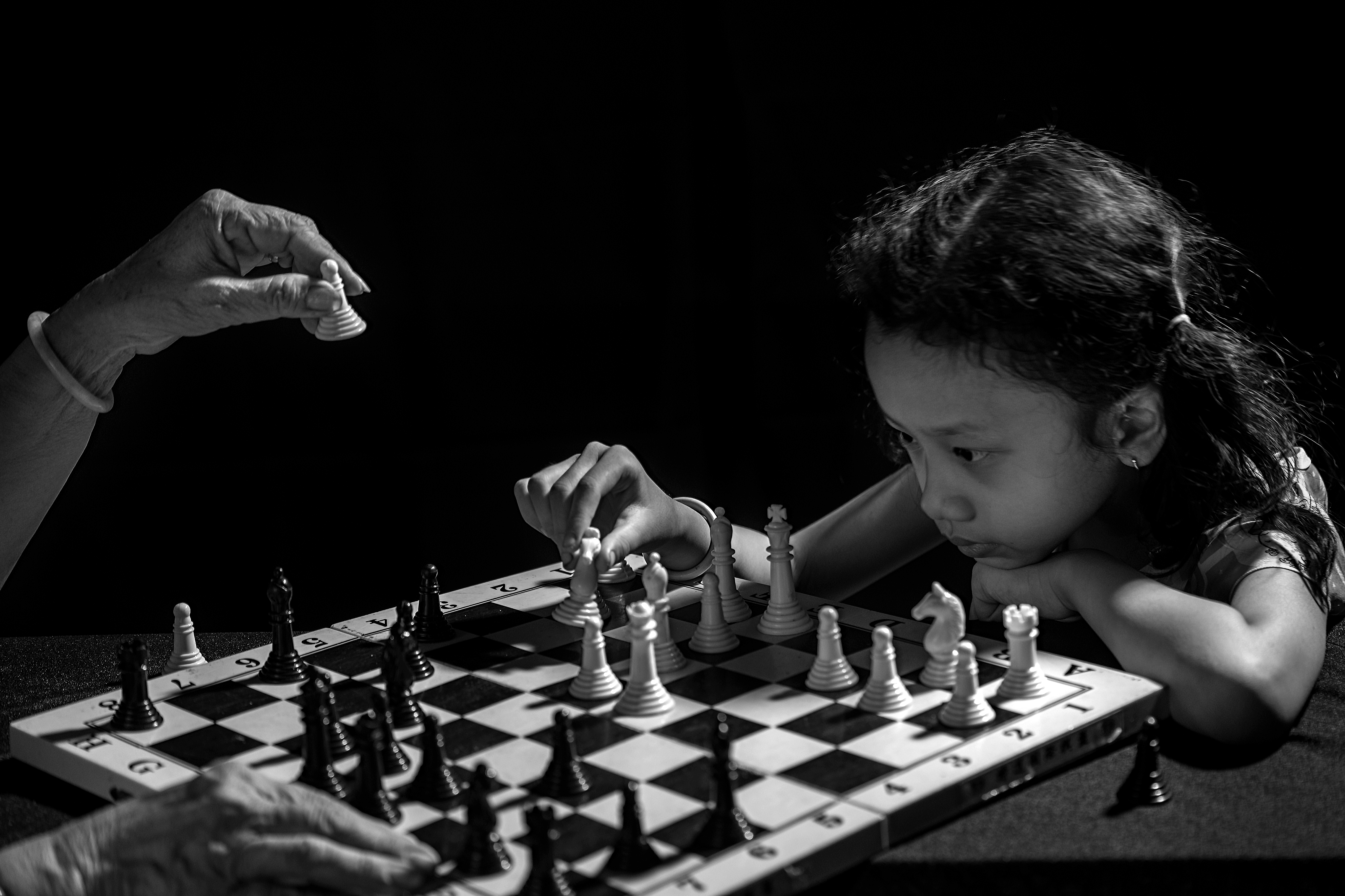 Black and white photo of a young girl puzzling out her next move in a game of chess with her grandmother.