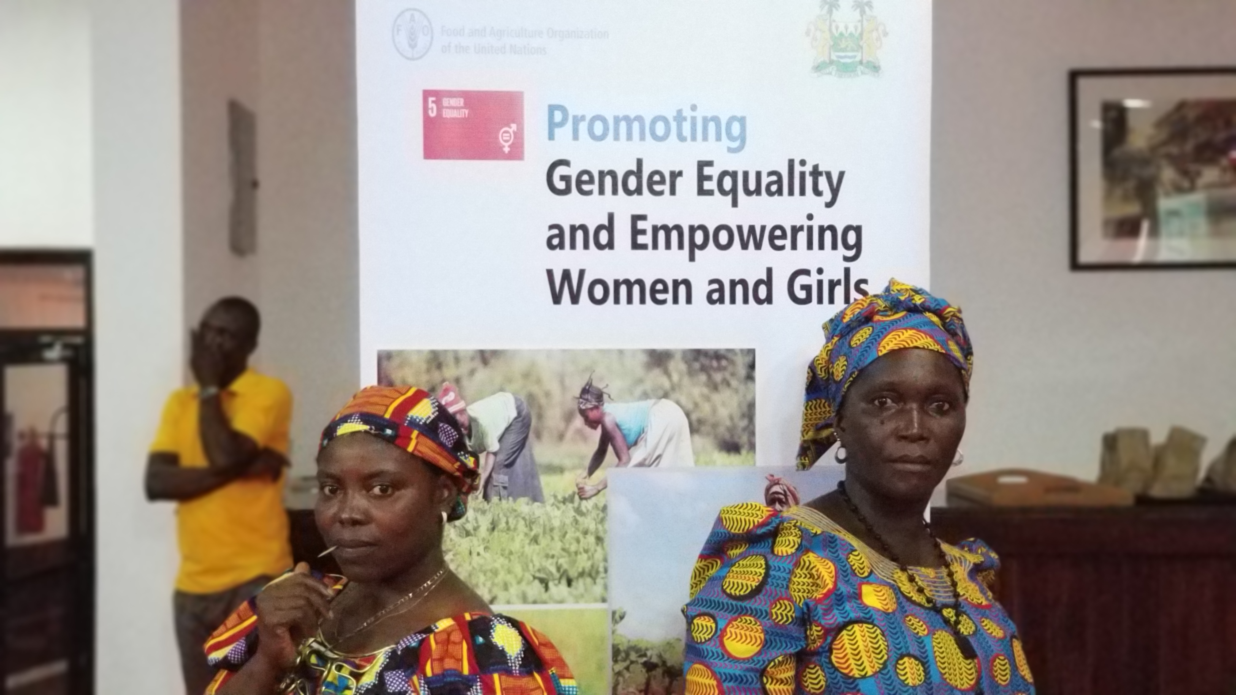 Two women stand powerfully in front of an banner promoting SDG 5: Gender equality and empowering women and girls.