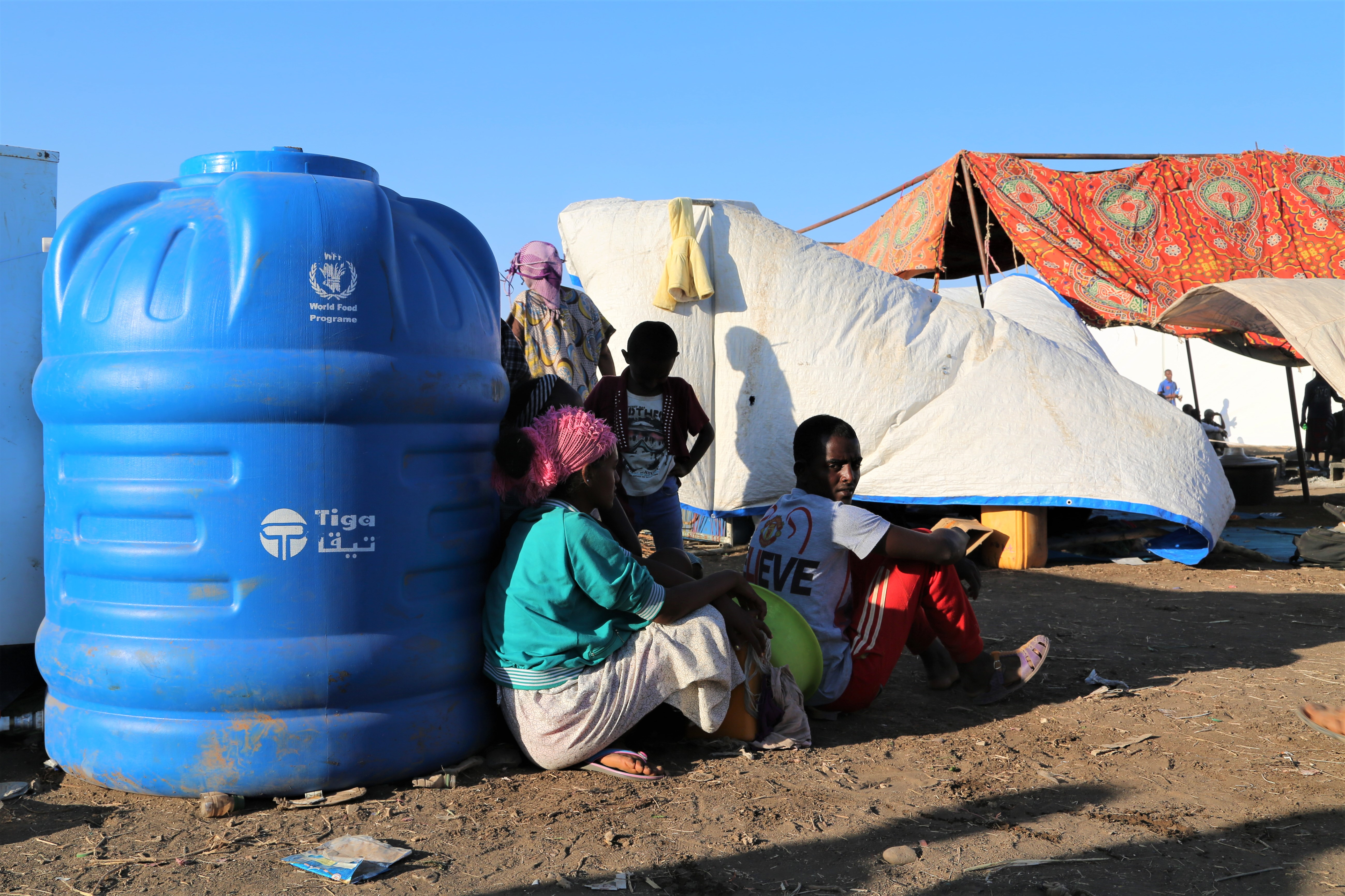 People sit against a large blue container of water at the camp.